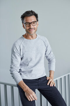 Portrait of smiling man with stubble wearing grey sweatshirt and glasses