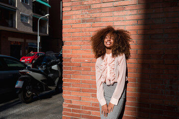 Portrait of smiling young woman with afro hairdo leaning against brick wall in the city Fotomurales