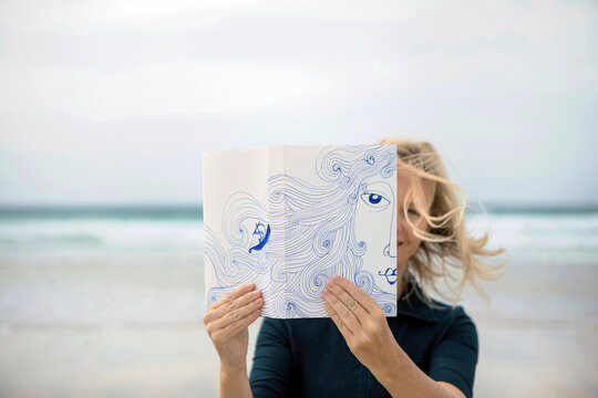 Woman covering face with book, reading poetry on beach