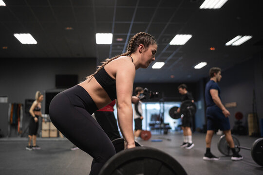 Woman picking barbell with people exercising in background at gym
