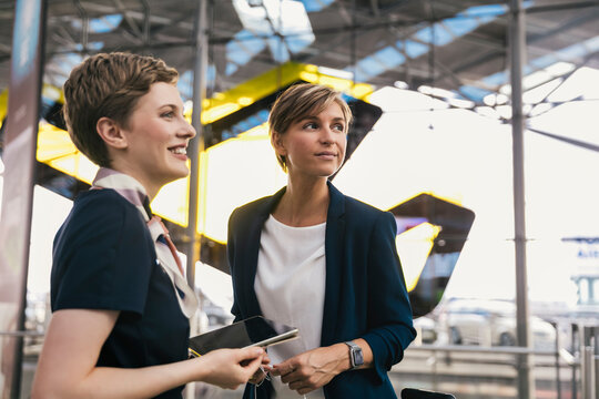 Smiling airline employee with tablet and businesswoman at the airport