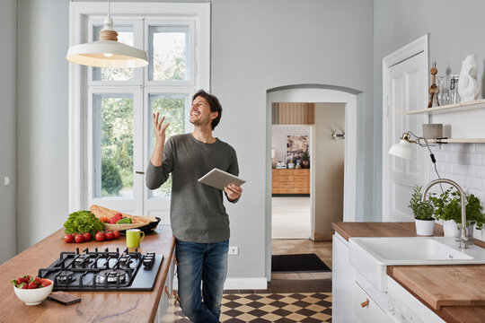 Happy man using tablet in kitchen looking at ceiling lamp