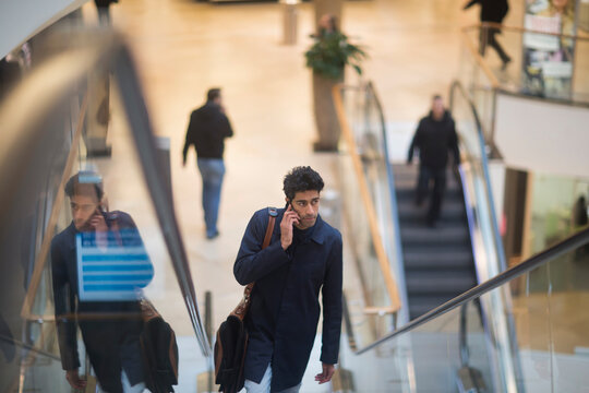 Man on the phone standing on escalator in a shopping mall
