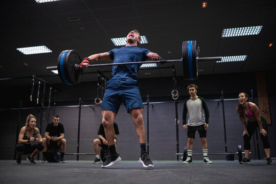 Adaptive athlete jumping while lifting barbell with people cheering in background at gym