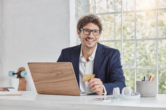 Portrait of smiling businessman with laptop on desk holding credit card
