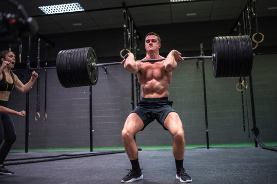 Women cheering man lifting barbell up while standing at gym