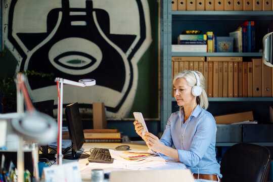 Mature woman talking on the phone with headphones, sitting in architect's office