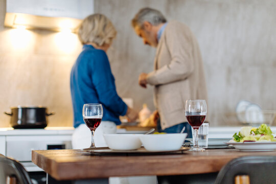 Red wine glasses on kitchen table with mature couple preparing dinner