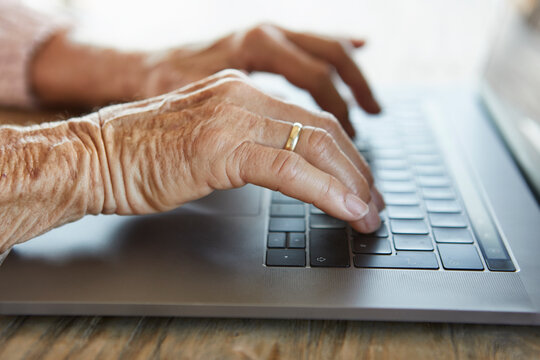 Hand of senior woman typing on keyboard of laptop, close-up