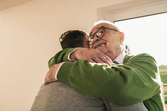 Smiling senior man hugging young man