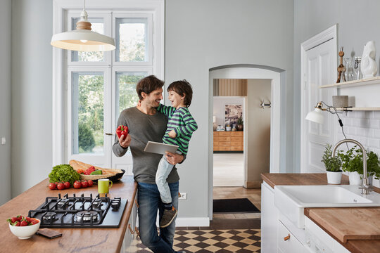Happy father and son with bell pepper and tablet in kitchen