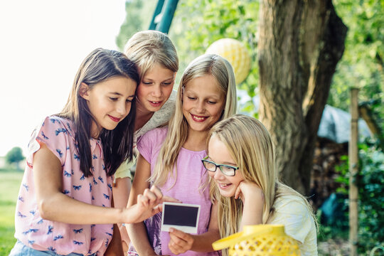 Happy girls looking at instant photo on a birthday party outdoors
