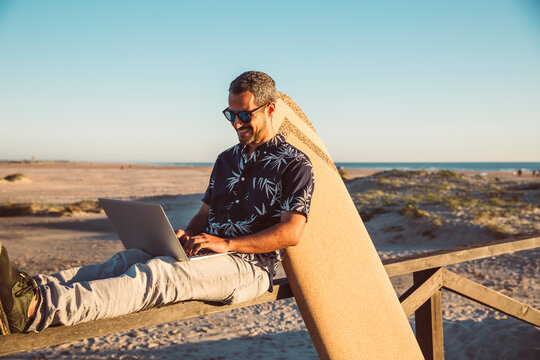 Man sitting at the beach, using laptop, with surfboard leaning on fence