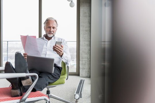 Mature businessman working on office chair with feet up
