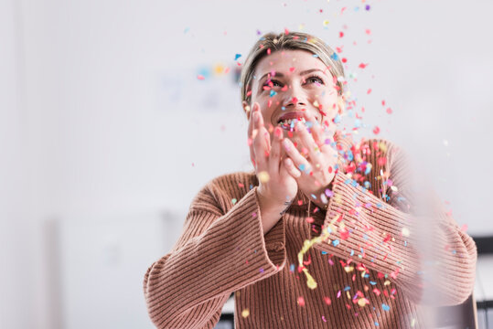 Happy young woman throwing confetti in the air
