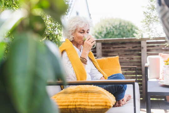 Mature woman drinking juice while sitting on sofa in balcony
