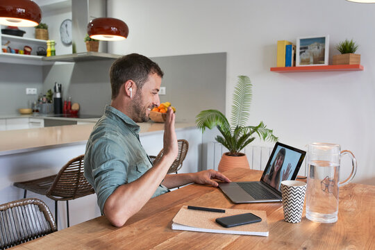 Smiling businessman waving at female colleague through video call on laptop while working from home