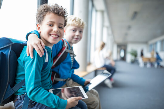 Portrait of two smiling schoolgboys with tablet embracing