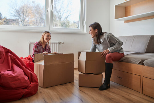 Two happy young women unpacking cardboard boxes in a room