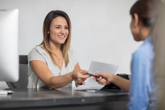 Smiling woman handing over pen to client at desk