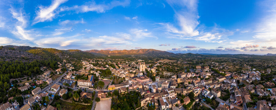Spain, Mallorca, Calvia, Helicopter panorama of old town at dusk with Serra de Tramuntana range in background