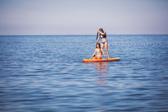 Friends surfing on stand up paddle board in sea during sunny day