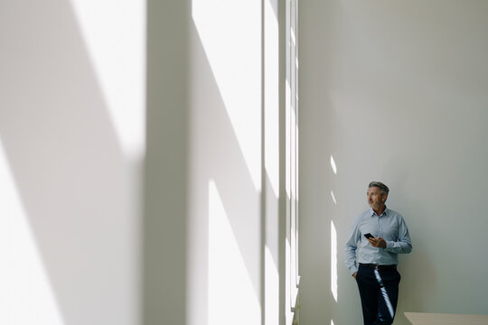 Businessman with looking at window while leaning on wall at office