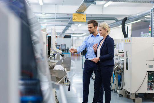Confident young engineer discussing with businesswoman while pointing at machinery in factory