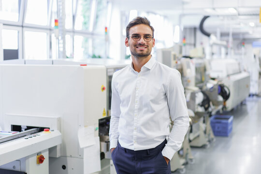 Smiling young businessman standing with hands in pockets at illuminated factory