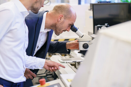 Young technician pointing to male colleague looking through microscope at laboratory