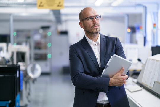 Businessman holding digital tablet while looking away at bright factory