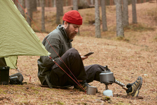 Young Traveller Using Gadget In Forest