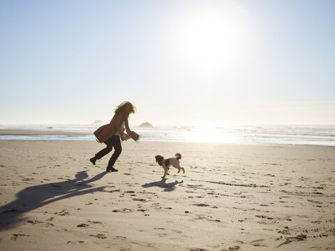 Young Women playing with dog on the beach