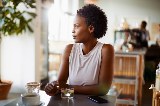 Young African American woman sitting alone at a cafe table