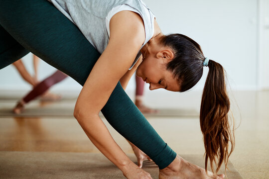 Smiling young woman practicing yoga in a gym class