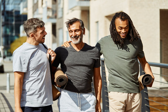 Smiling group of men walking outside after a gym session