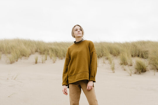 young woman in golden monochromatic outfit standing on the coast in the sand