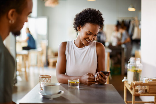 Smiling woman sitting with a friend and checking her phone