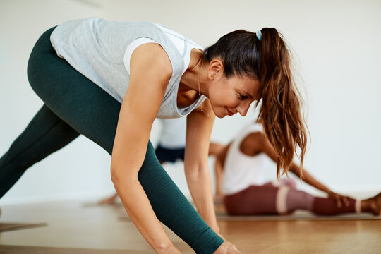 Smiling young woman doing yoga in a health club class