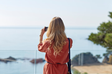 Woman on holiday taking photo of a beautiful view Fotomurales