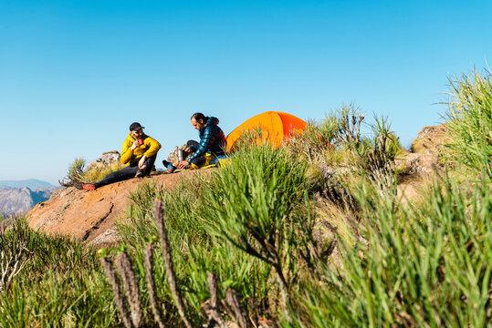 Adventurers enjoying hot drink during camping