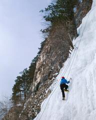 Climber climbs on a frozen waterfall