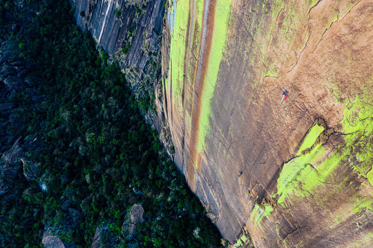 Aerial shot of rock climber on belay fixing rope