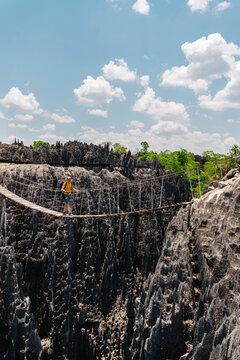 Adventurer on rope bridge over rocky terrain