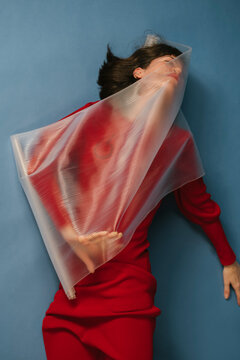woman with red dress and transparent plastic sheet