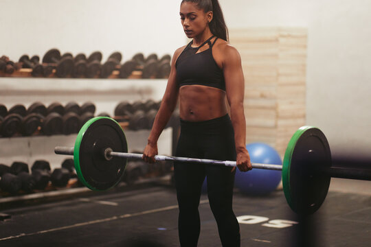 Muscular young woman lifting heavy weights in a gym