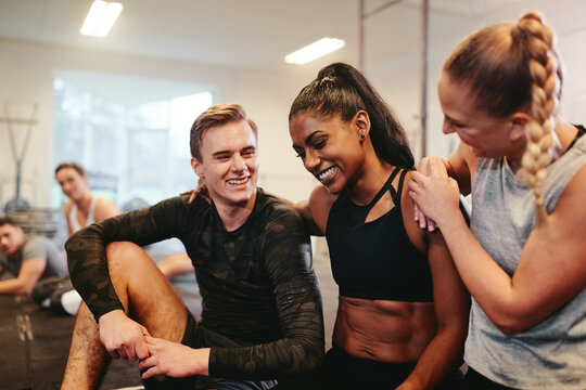 Diverse group of laughing friends talking together at the gym
