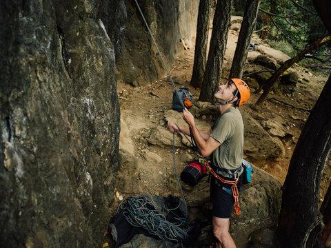 Man belaying a rock climber at base of mountain