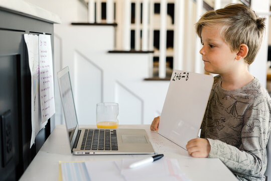 Little boy being homeschooled and doing work online