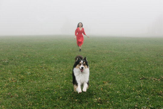 Girl in red dress running with dog